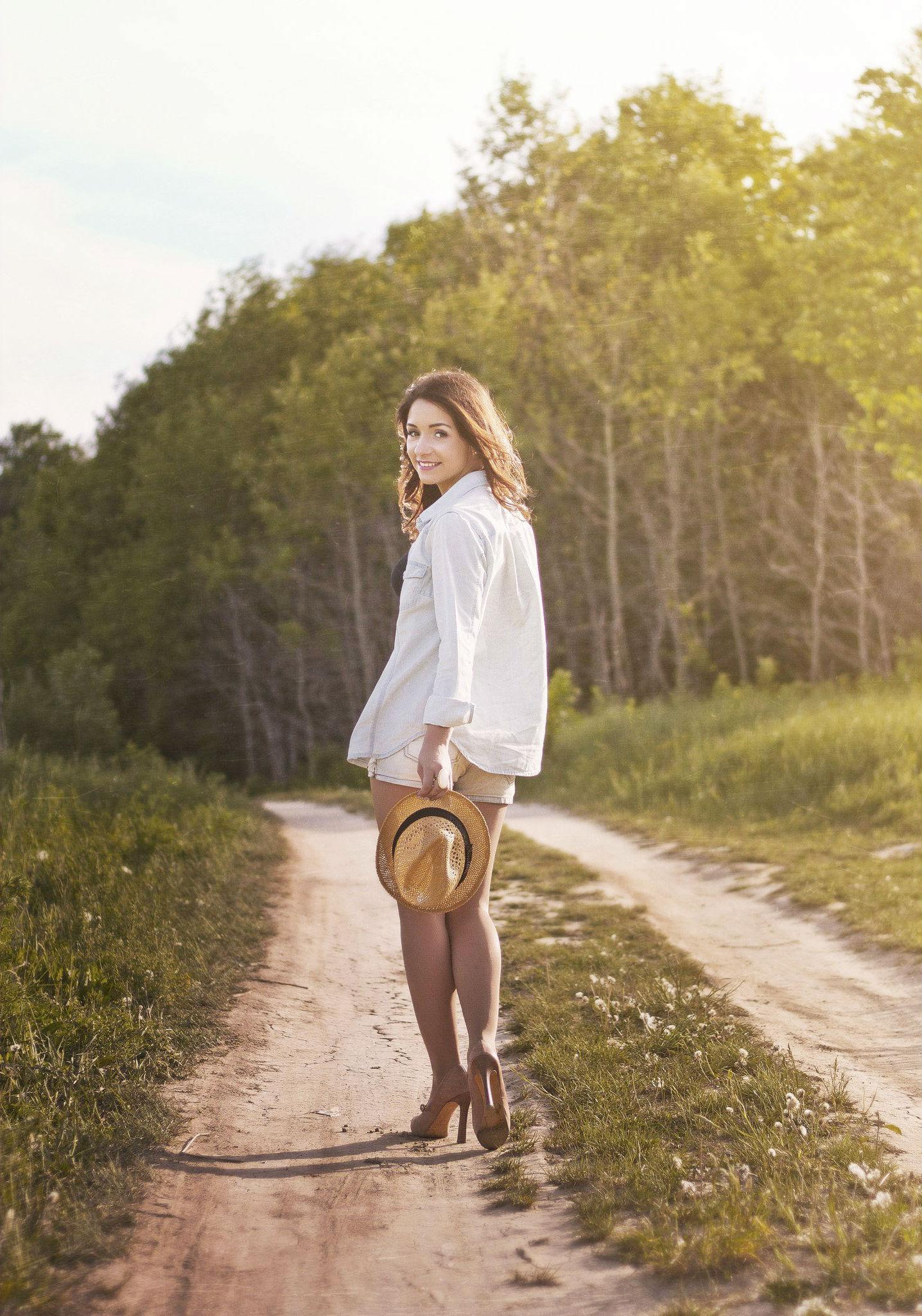 Девчонка-шатенка  в колготках и шортах прогуливается по дорожке