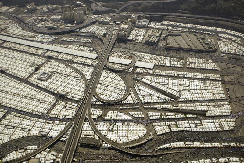 23. Мусульманские паломники, идущие вдоль палаток в долине Мина, близ Мекки, Саудовская Аравия, 9 де