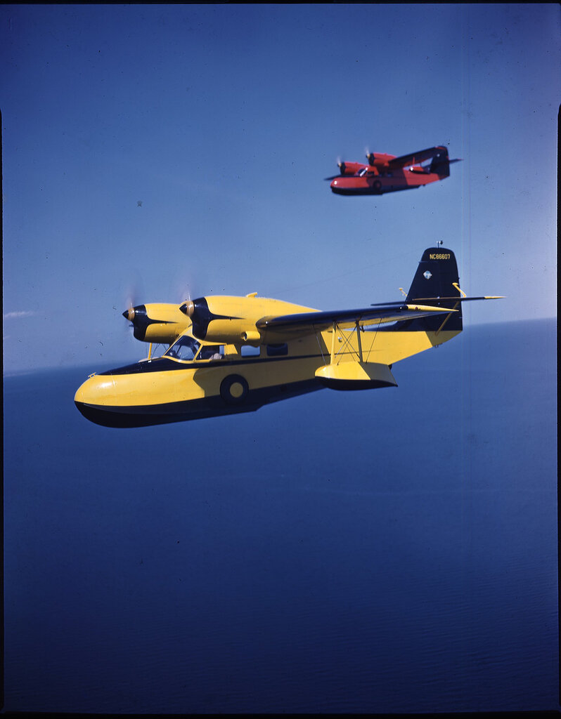 Two Grumman G-44 Widgeons (rn NC86607; distant aircraft's rn is not visible) in flight probably over Long Island, New York