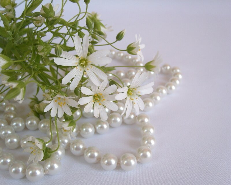 Белые цветы и бусы из жемчуга.