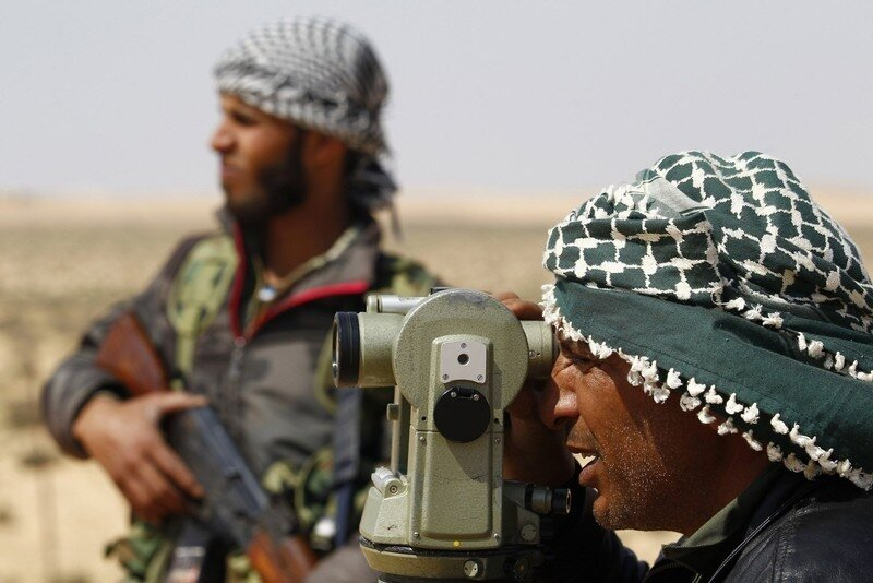 A rebel fighter surveys a sight on the road to the east of Brega in Libya