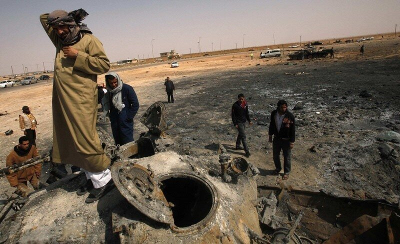 A rebel gestures atop a destroyed tank belonging to forces loyal to Libyan leader Gaddafi after an air strike by coalition forces in Ajdabiyah