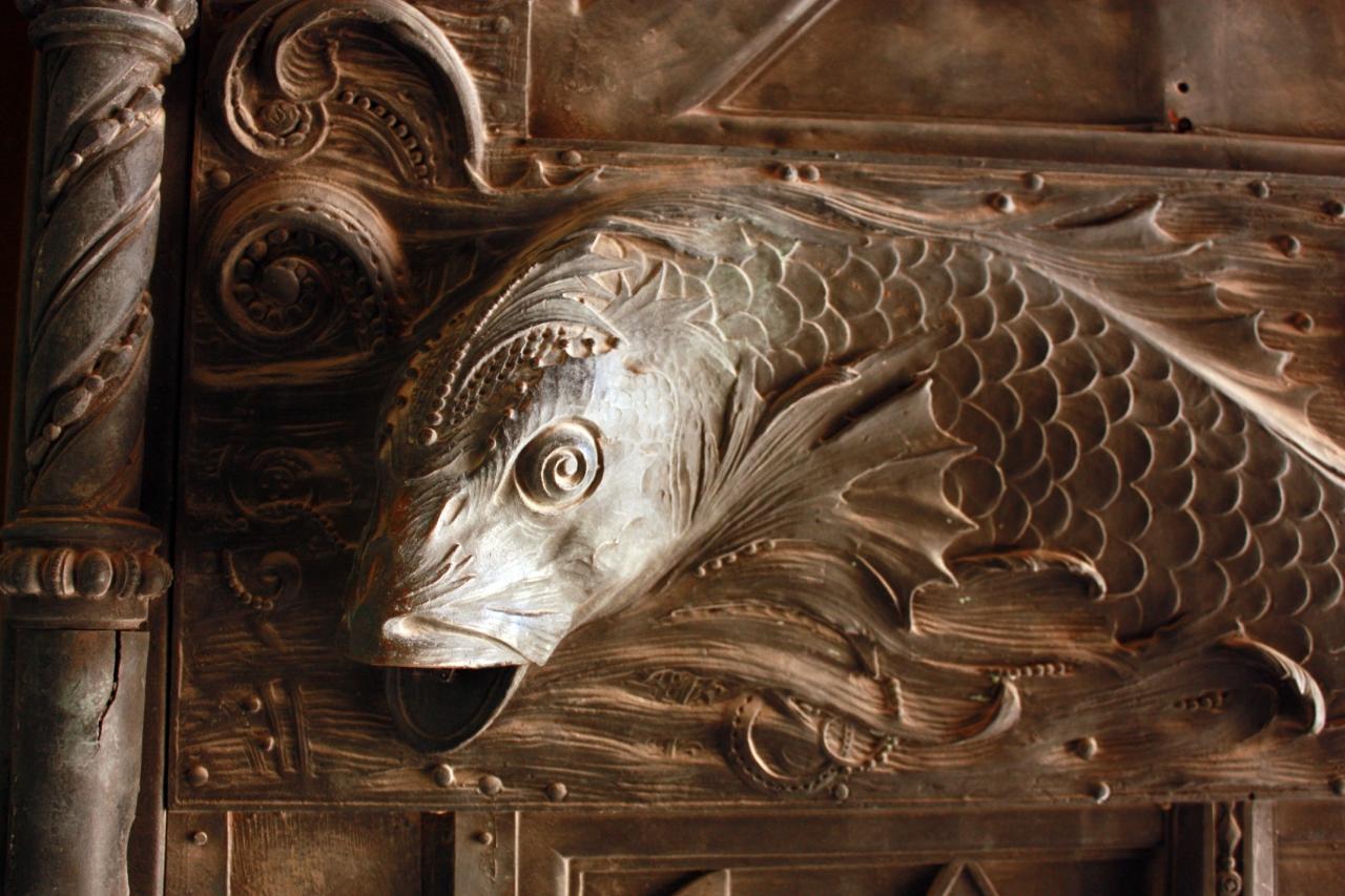 Скульптурное изображение рыбы на дверях собора.