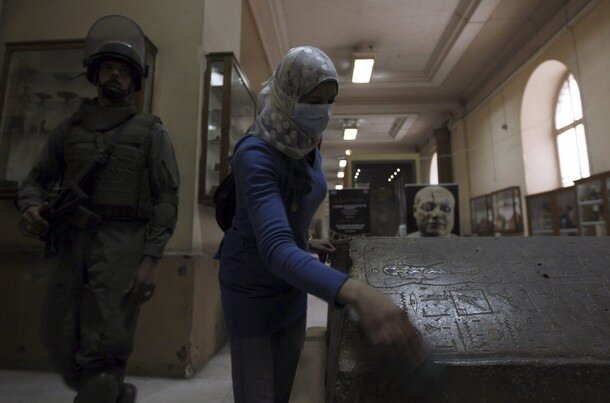 A member of the Egyptian Army special forces moves past a mummy being cleaned by a worker in the Egyptian Museum, in Cairo