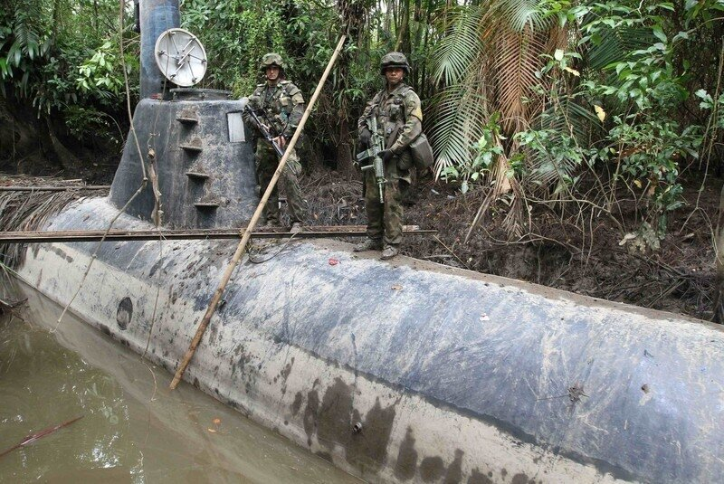 Members of the Colombian Navy stand guard on top of a seized submarine built by drug smugglers in a makeshift shipyard in Timbiqui
