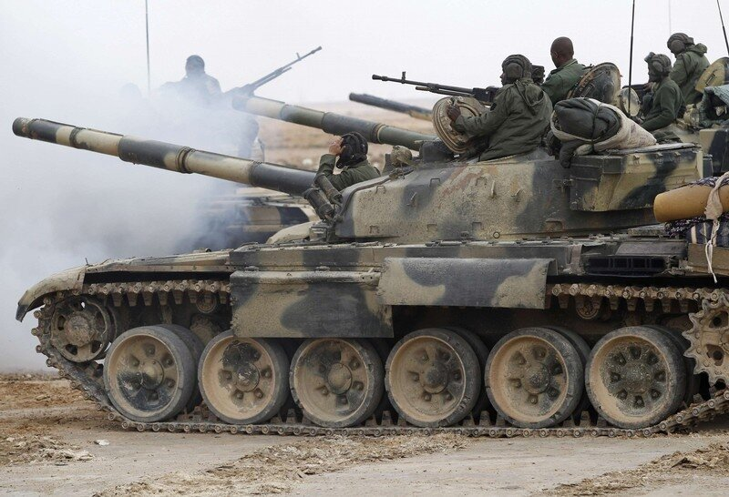 Libyan government soldiers and their tank move at the west gate of town Ajdabiyah
