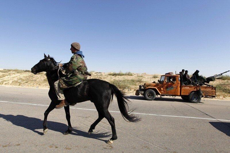 A rebel rides a horse along the road outside Brega