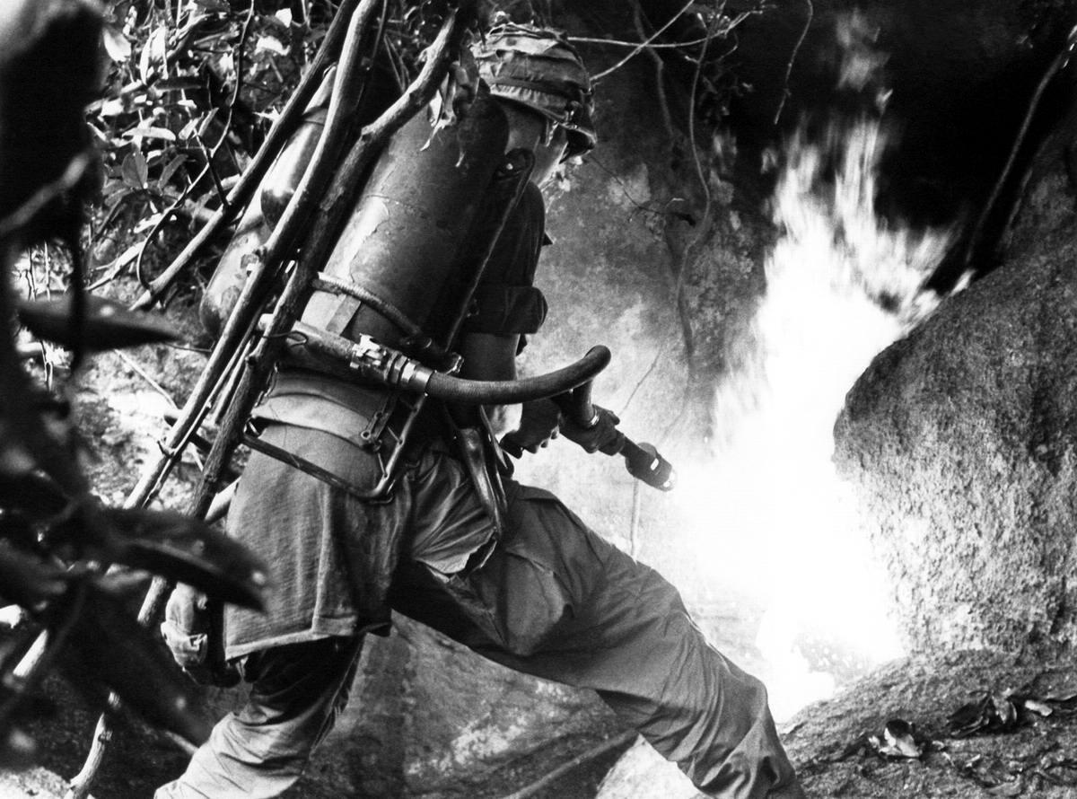 Солдат американской 1-й кавалерийской дивизии направил свой огнемет в сторону входа в пещеру в долине An Lao в Южном Вьетнаме