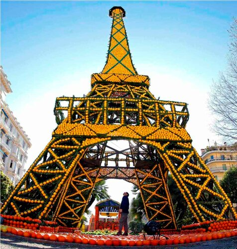 A worker looks at an Eiffel tower made from lemons and oranges during the lemon festival in Menton, southern France, February 16, 2012. Some 145 metric tons of lemons and oranges were used to make displays during the 79th festival, which is themed