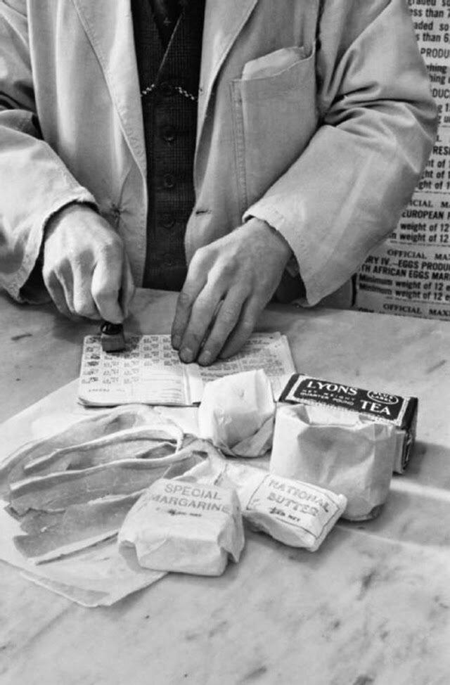19. Лавочник ставит штамп на продуктовые талоны миссис Оливии Дэй во время ее похода по магазинам. На переднем плане можно увидеть чай, сахар, «национальное масло», маргарин, кулинарные жиры и сало. Она имеет право отоварить талоны в течение одной недели