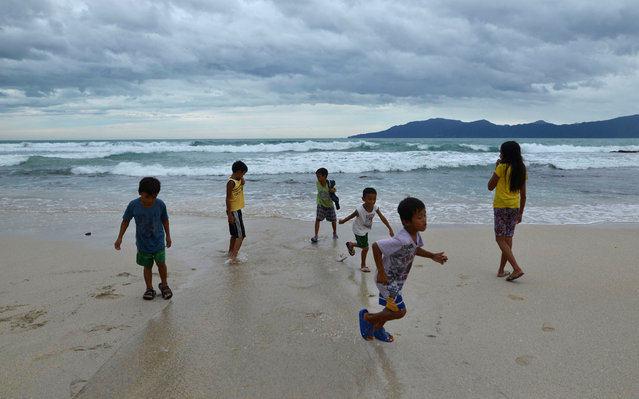 Children play along an empty beach after Typhoon Haima struck Pagudpud, Ilocos Norte, in northern Ph