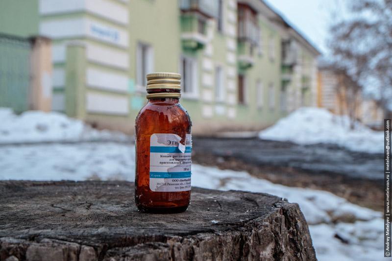 бутылек спирта на фоне дома, спирт стоящий не пне