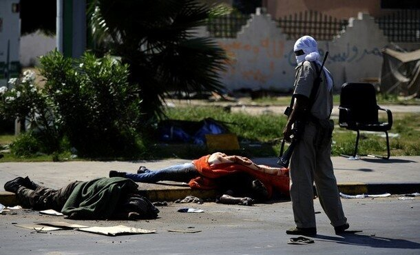 A Libyan rebel stands next to the bodies