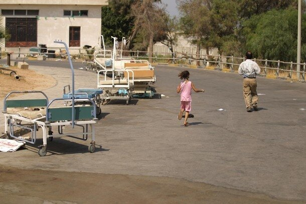A Libyan girl and her father run past st