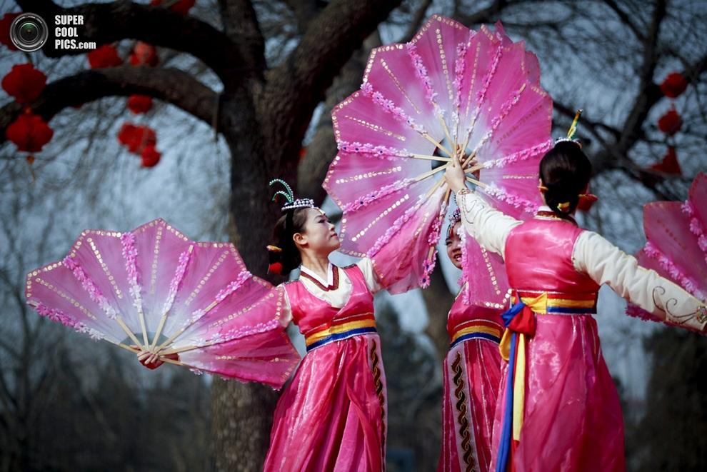 Танцоры в национальных корейских костюмах во время представления на Празднике весны в Пекине. (E