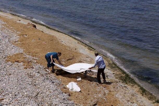 Civilians cover the body of a man found along a beach in Tripoli