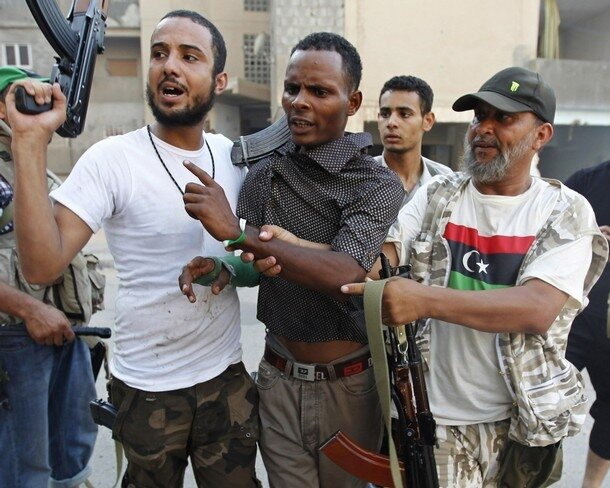 Libyan rebel fighters detain a mercenary during a fight for the final push to flush out Muammar Gaddafi's forces in Abu Salim district in Tripoli