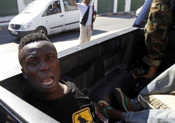 A man accused of being a Libyan leader Muammar Gaddafi loyalist mercenary sits in a rebel vehicle in Tripoli