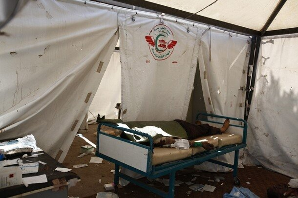 A body is seen at a field hospital in the Abu Slim area in Tripoli