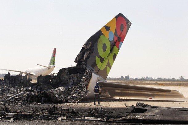 A cameraman works near a destroyed Afriqiyah Airways aircraft at the Tripoli Airport