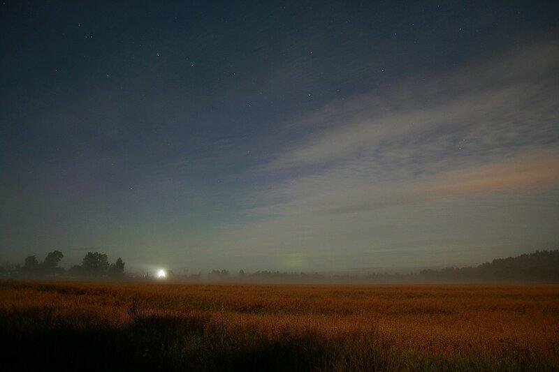 Огни деревни Жданухино в тумане, звёздное небо с Большой Медведицей и зелёное зарево полярного сияния на горизонте за облаками