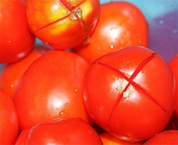 томаты, надрезанные крест-накрест для снятия шкурки