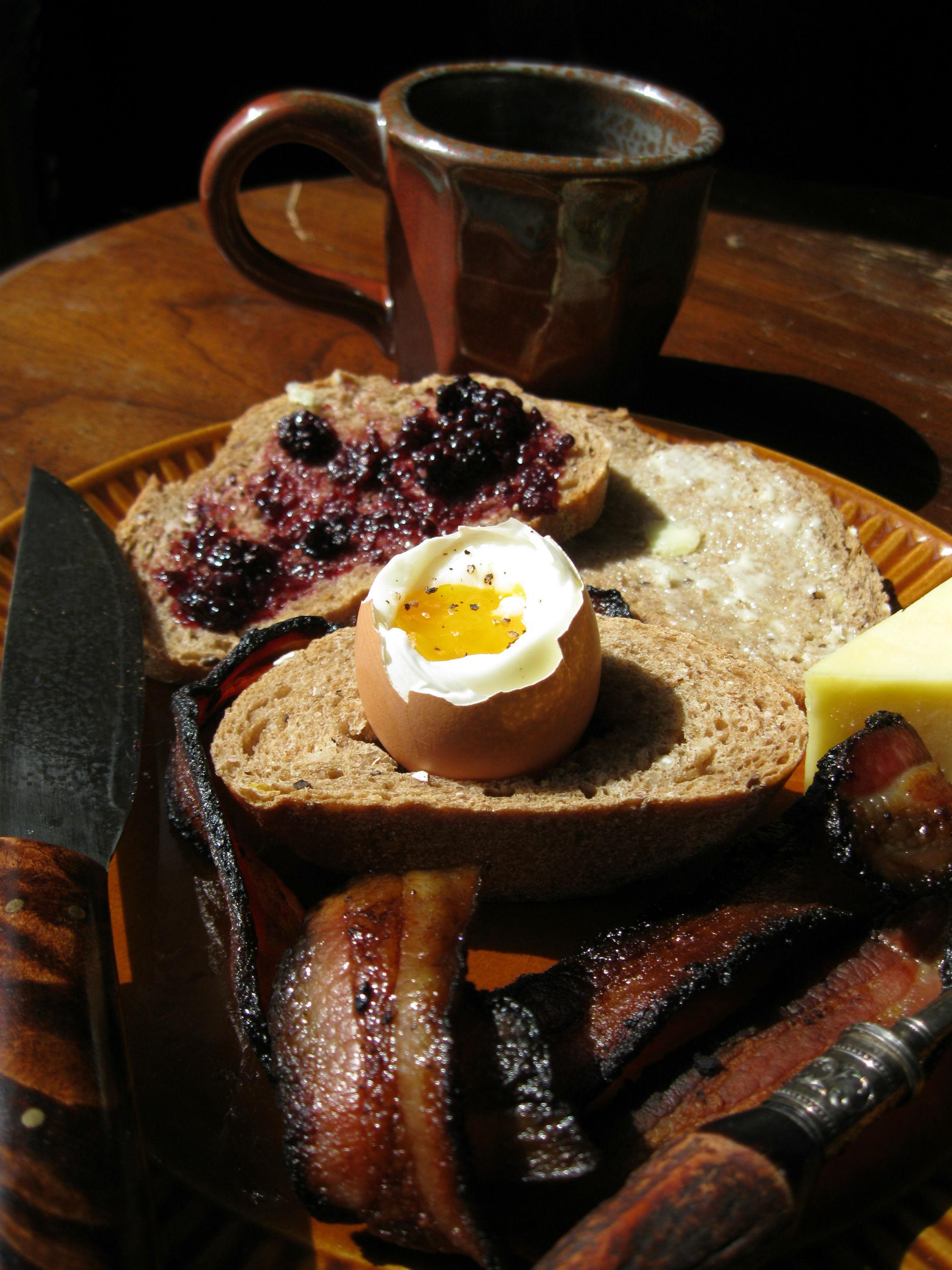 Ингредиенты: 2 яйца, 6 полосок бекона, 4 ломтика домашнего хлеба, сливочное масло, мёд, ягодный джем