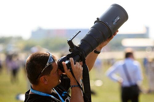 Человек с большим объективом фотографирует самолеты