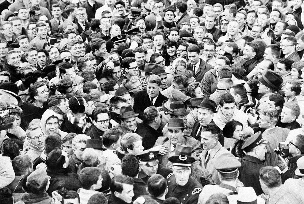 избранный Президент Джон Ф. Кеннеди (в центре) в толпе студентов Гарварда в Гарвардском дворе в Кембридже, 9 января 1961 года.когда студенты прорвали полицейский барьер.