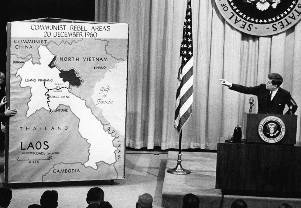 """Президент США Джон Ф. Кеннеди указывает на карту Лаоса во время пресс-конференции в Вашингтоне, в марте 1961 года,после заявления, что коммунистическая угроза в Лаосе является """"потенциально опасной""""."""