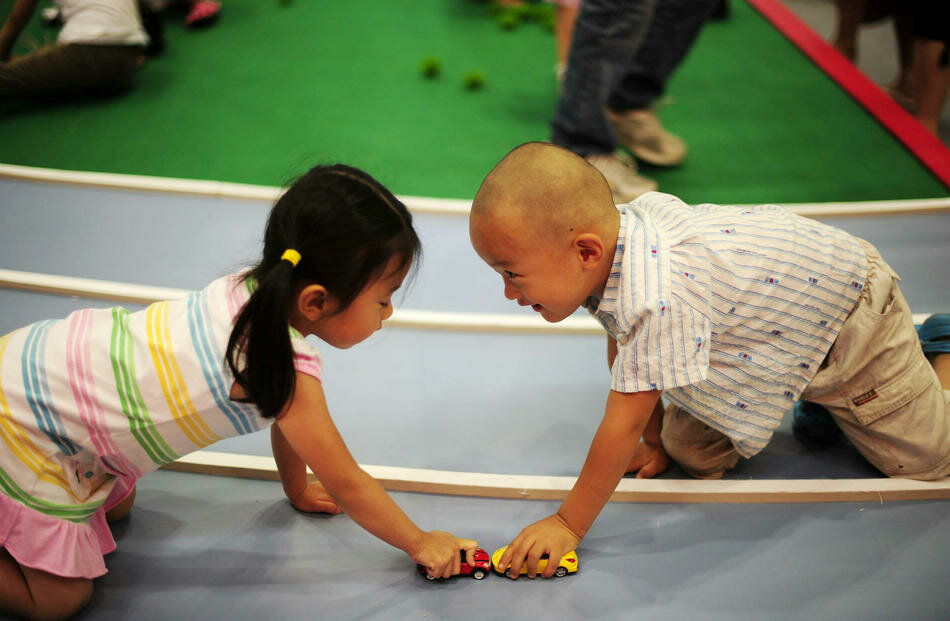 Chinese children play with toy cars at a