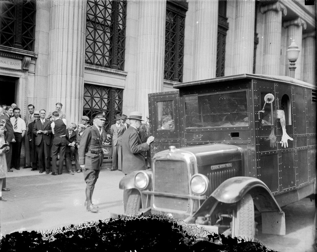 Colorado National Bank employee loads bags of gold into an armored car at 17th and Champa Streets in Denver, Colorado, 1933