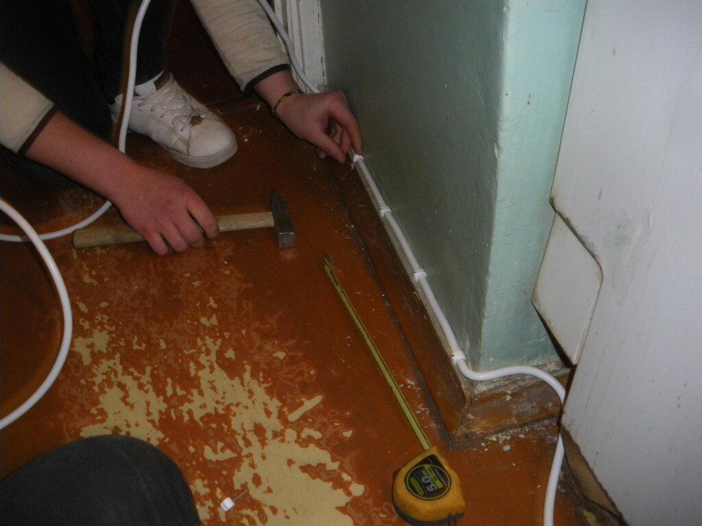 На фото показано, как прибить провод (кабель) к деревянному плинтусу с использованием пластиковых скоб.