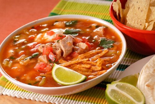 A bowl of chicken and tortilla soup with lime