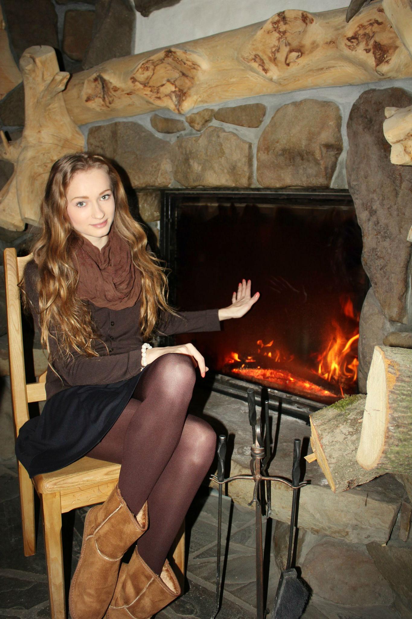 Светлорусая девушка в колготках возле камина