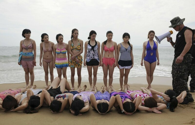 Trainees dressed in swimming suits follow instructions of trainer during training session in Sanya