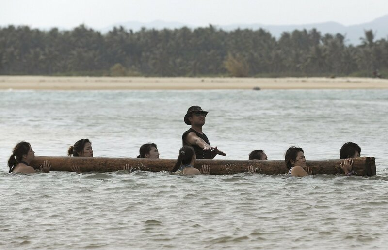 Trainees dressed in swimming suits carry log on their shoulders as they walk through sea under instructions of trainer in Sanya