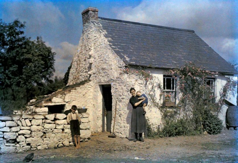 Семья стоит рядом со своим коттеджем в графстве Корк.