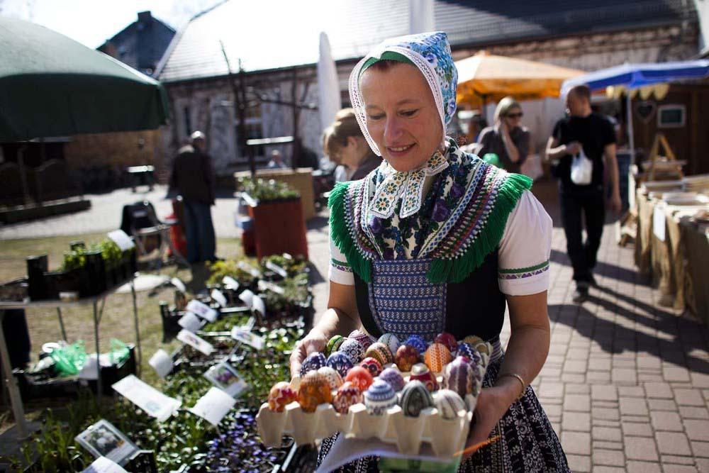 1. Сильвия Паноша в традиционном лужицком платье несет коробку яиц с традиционными узорами на рынке