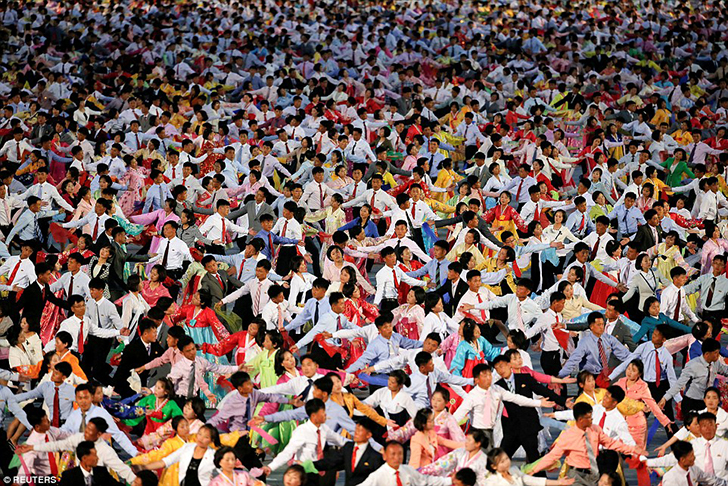 Ярко одетые граждане Северной Кореи танцуют на площади в Пхеньяне. Главной целью съезда стало обозна