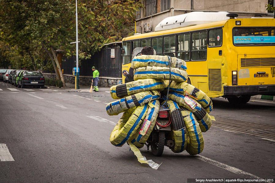 34. Мотоциклисты часто навьючивают на своего коня уйму всякого товара и так передвигаются по городу.