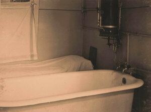 Вид части ванной комнаты с газовым нагревателем.