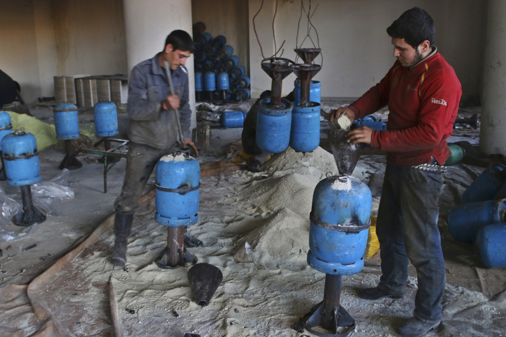 Men fill gas canisters with explosive for usage with a cannon named