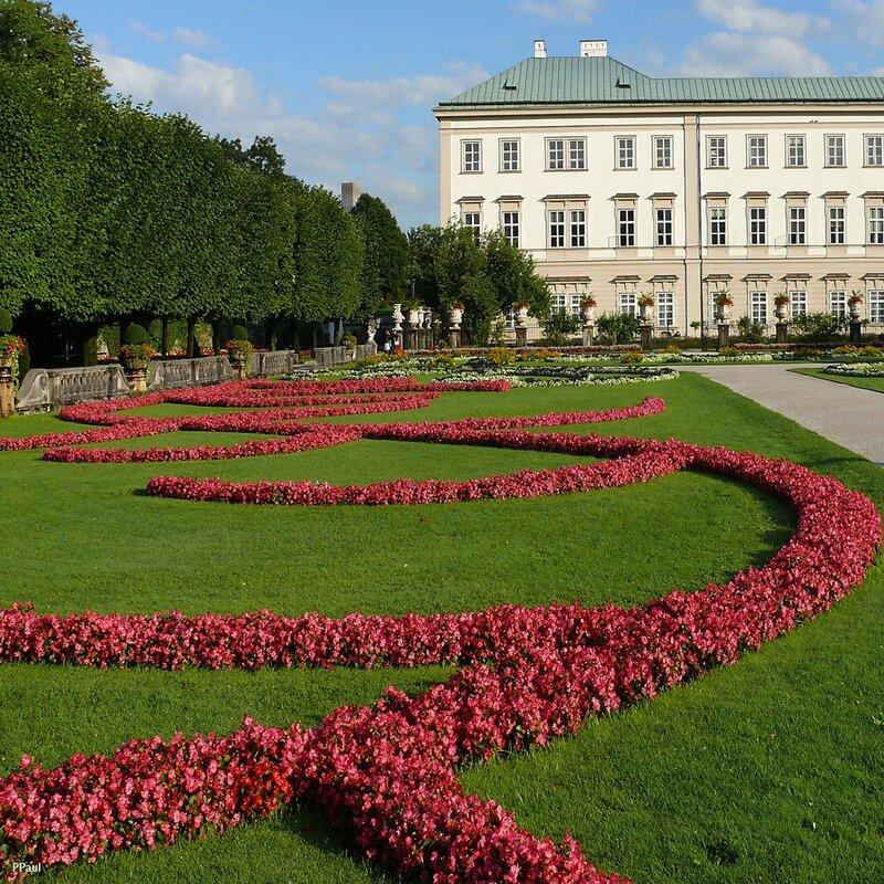 Партерные цветники, обрамляющие фонтан, выписывают монохромные арабески по зеленому ковру газона. На заднем плане - Дворц Мирабель.