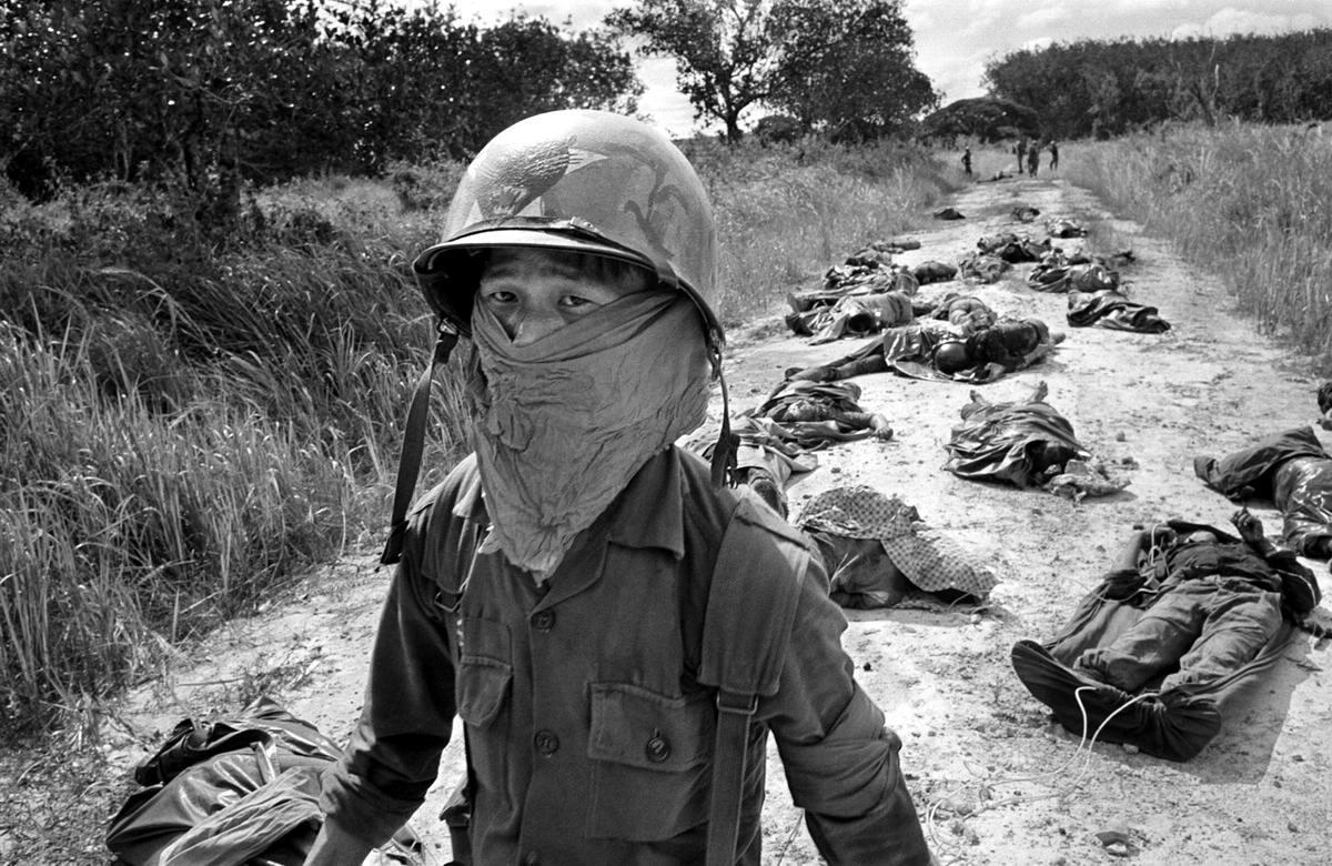 Южновьетнамский морпех в специальной повязке среди разлагающихся трупов американских и вьетнамских солдат, которые погибли в ходе боевых действий на каучуковой плантации компании Michelin в 70 км к северо-востоку от Сайгона