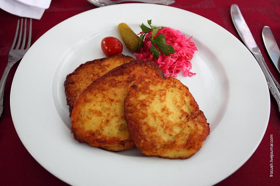 Оладьи наливные из рыбы с гарниром из соленой капусты и маринованных овощей, соус луковый с помидорами