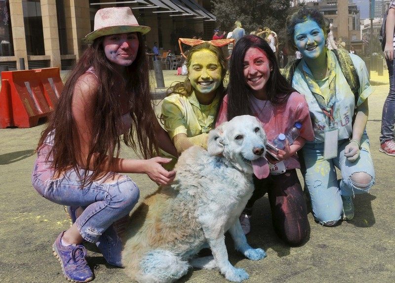 People pose with a dog covered in colour powder during the first color run called