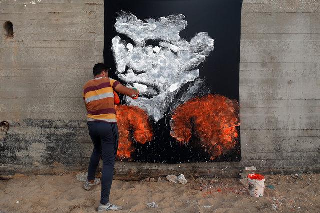Palestinian artist Osama Sebata, 26, uses boxing gloves to draw a mural of American boxing icon Muha