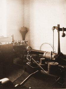Вид измерительных стендов весов, прибора для измерения давления и других в одном из цехов мастерской.