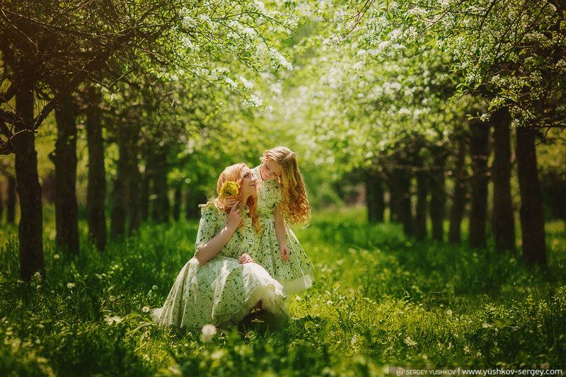 Мама и дочь в одинаковых платьях в цветущем саду